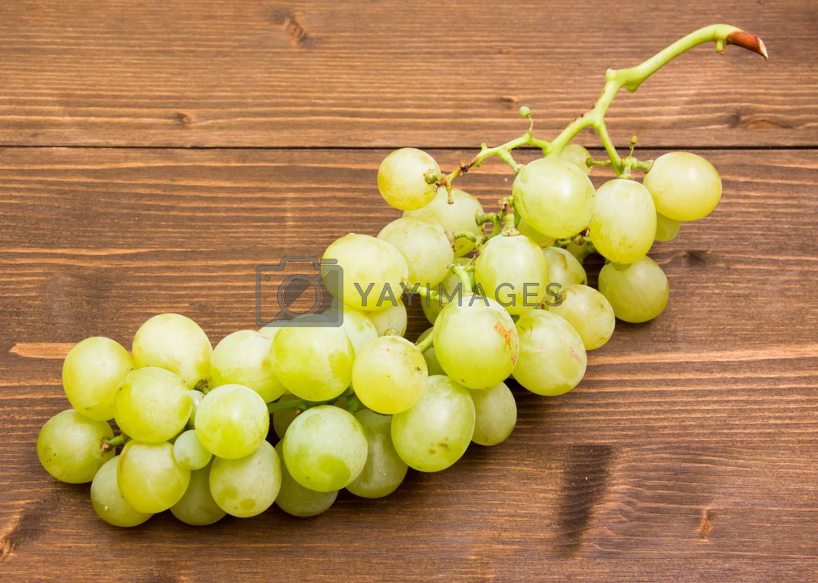 Bunch of grapes on wooden table seen from above