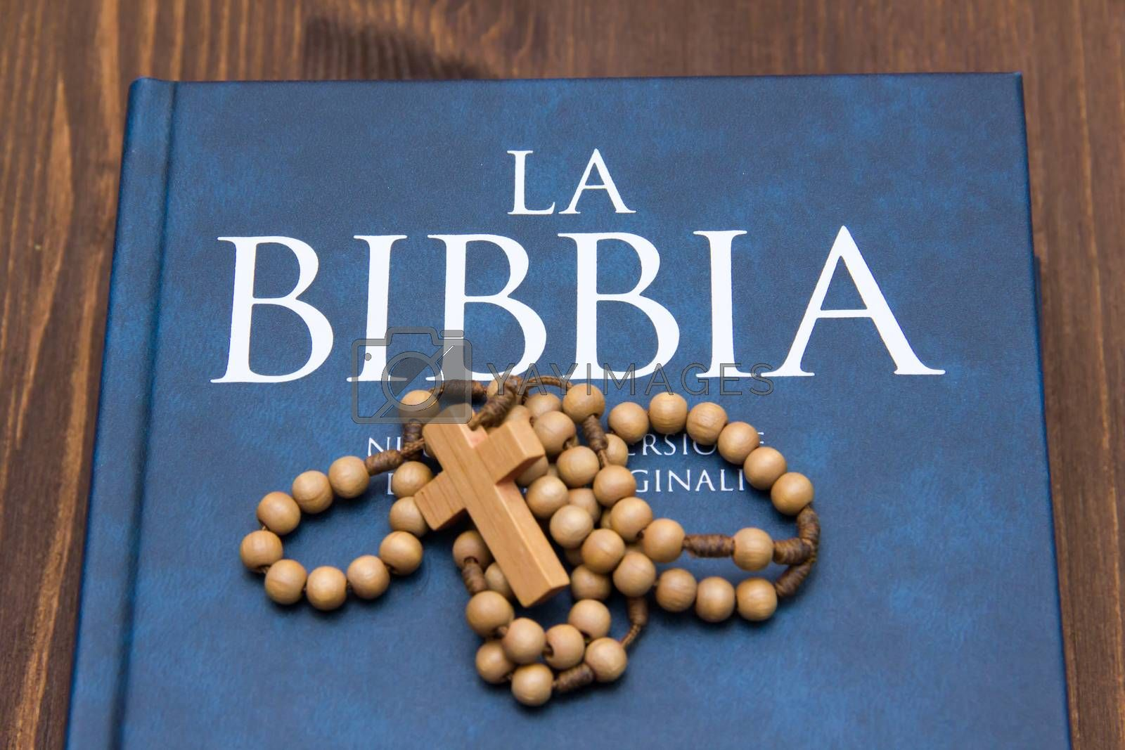 Bible with crucifix on wooden table