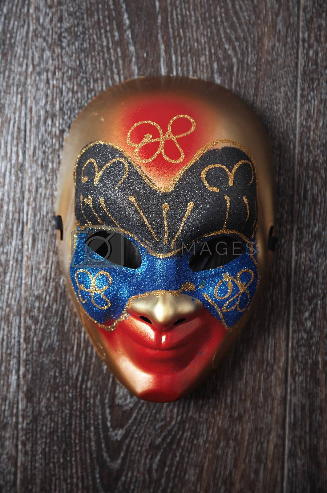 Carnival Venetian mask on a hardwood wall. Vertical photo