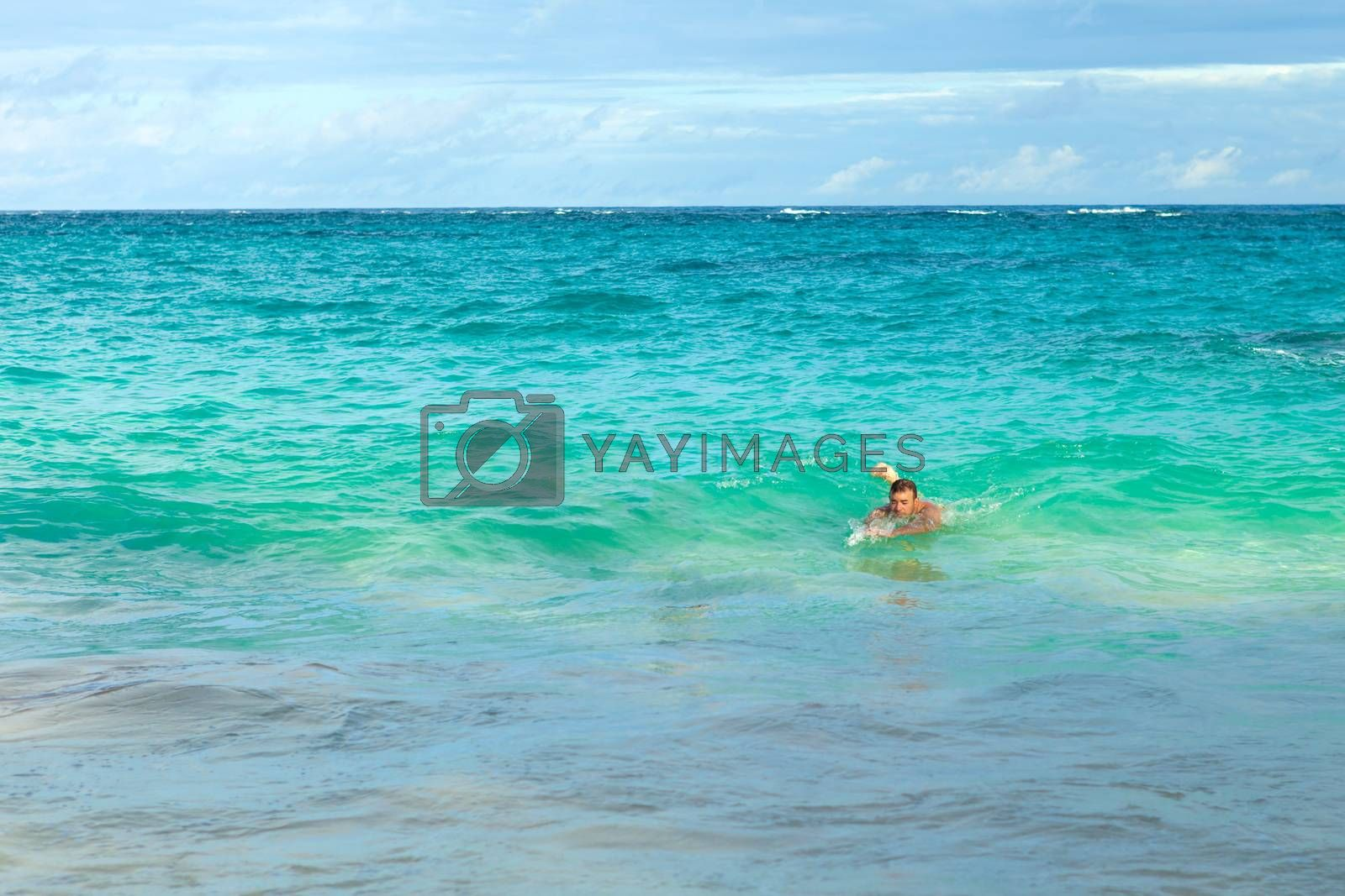 Man swimming alone in the waves body surfing at Bermudas John Smiths Bay beach.