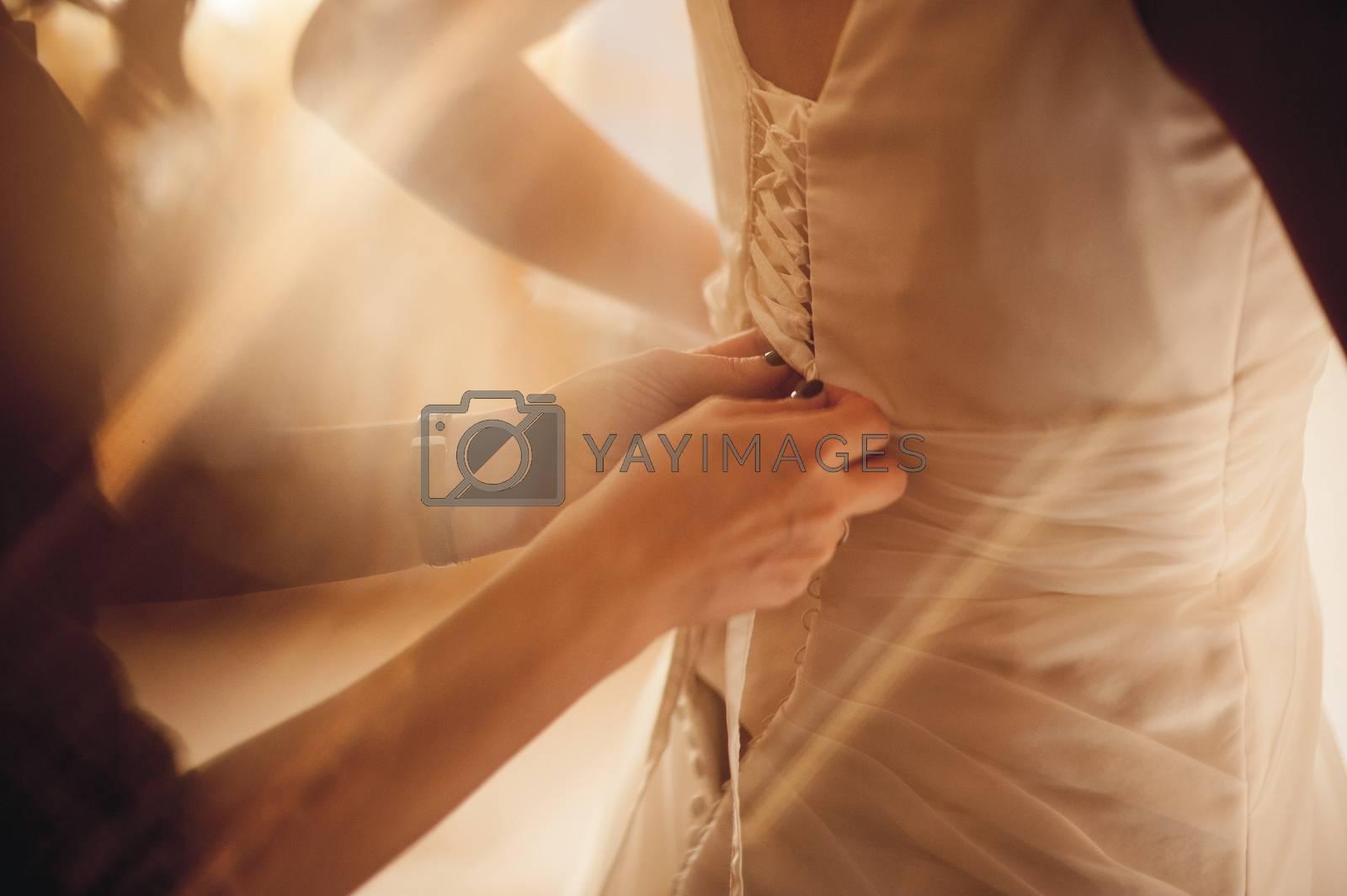 bride been helped putting on wedding dress