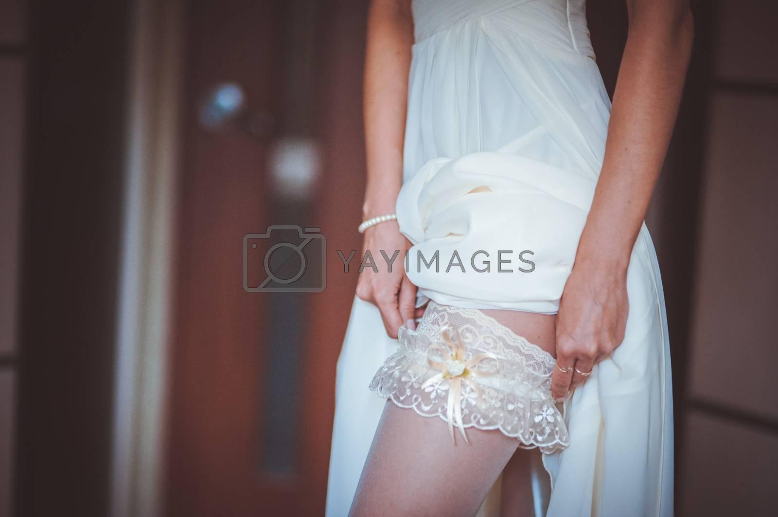 bride putting on white garter no face seen