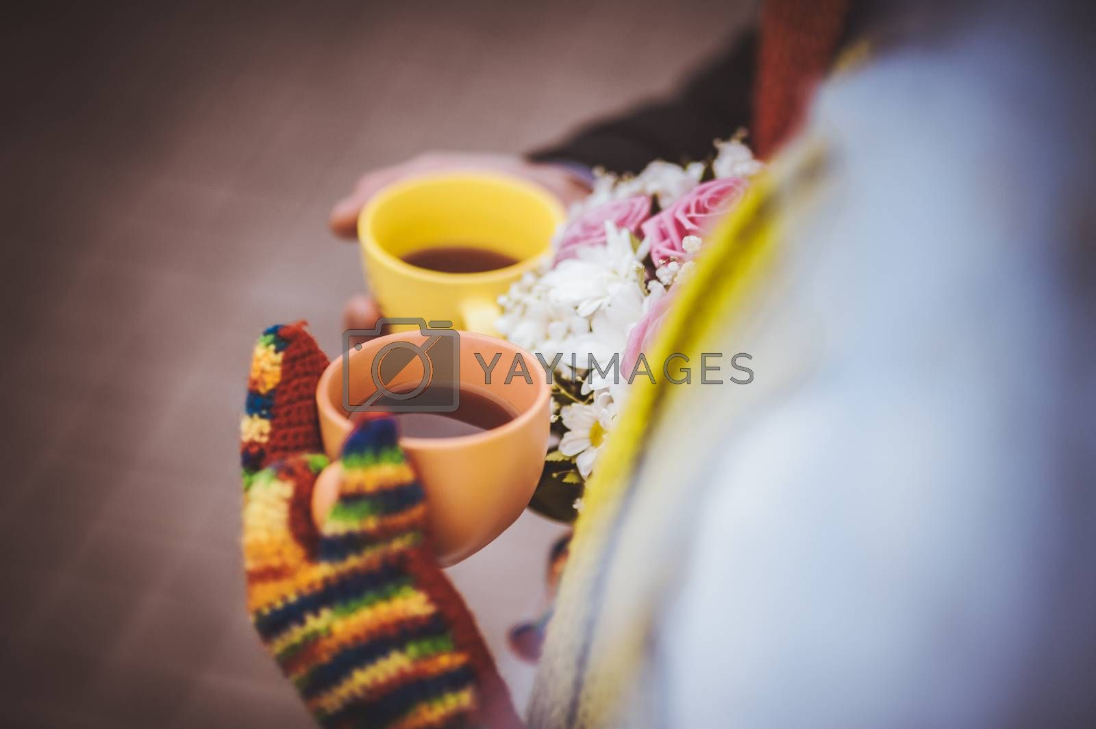 couple holding colorful cups of tea wearing mittens
