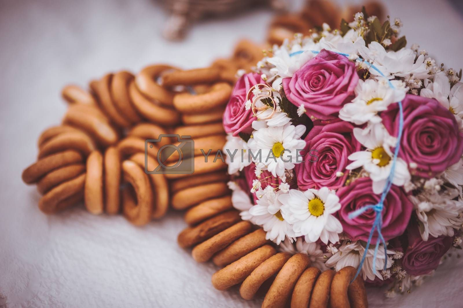 pink and white wedding bouquet next to russian bagels