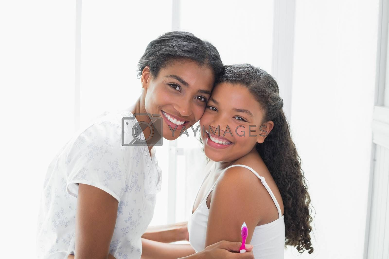 Pretty mother hugging her daughter smiling at camera at home in bathroom