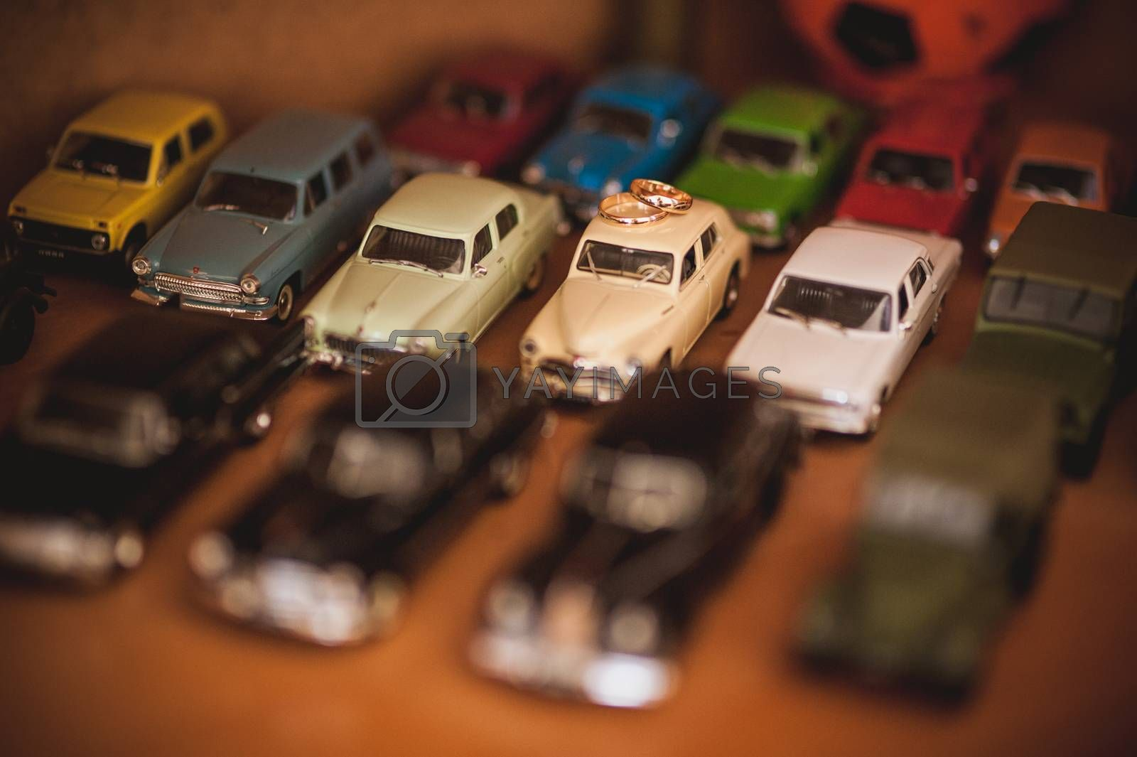 two gold wedding rings on top of toy car collection