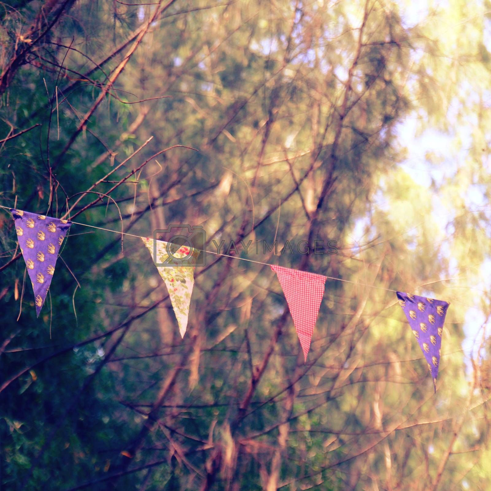 Colorful bunting flags hanging on tree with retro filter effect
