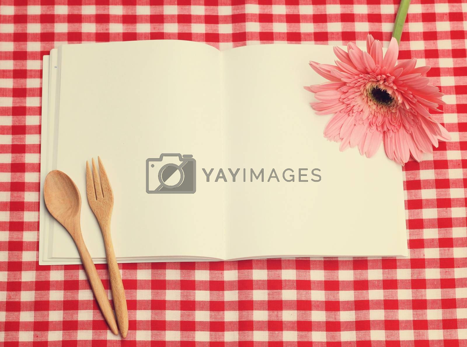 open blank recipe book on checkered tablecloth with retro filter effect