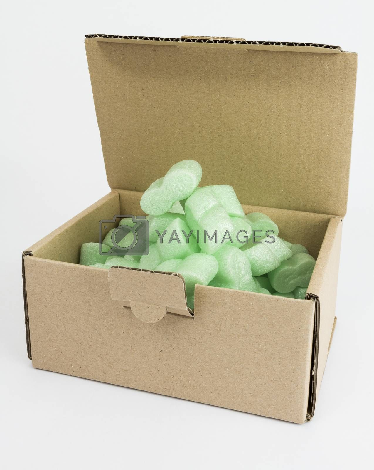 open packaging box with green foam on neutral grey background