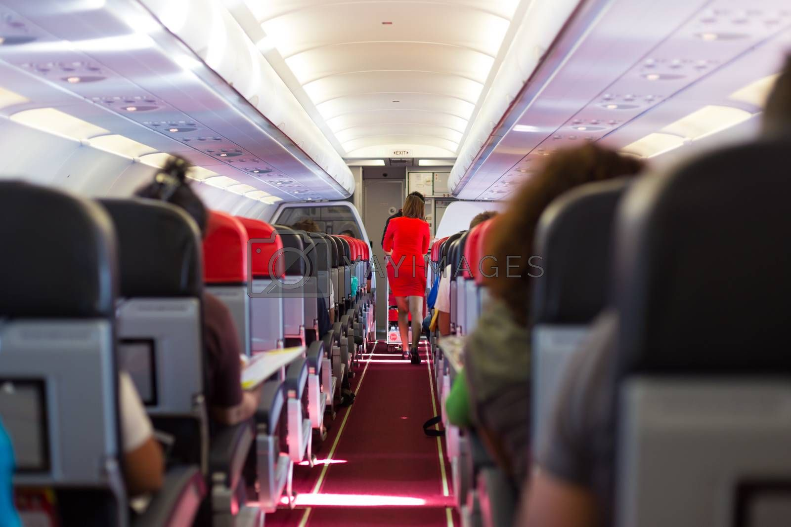 Interior of airplane with passengers on seats and stewardess in red uniform walking the aisle.