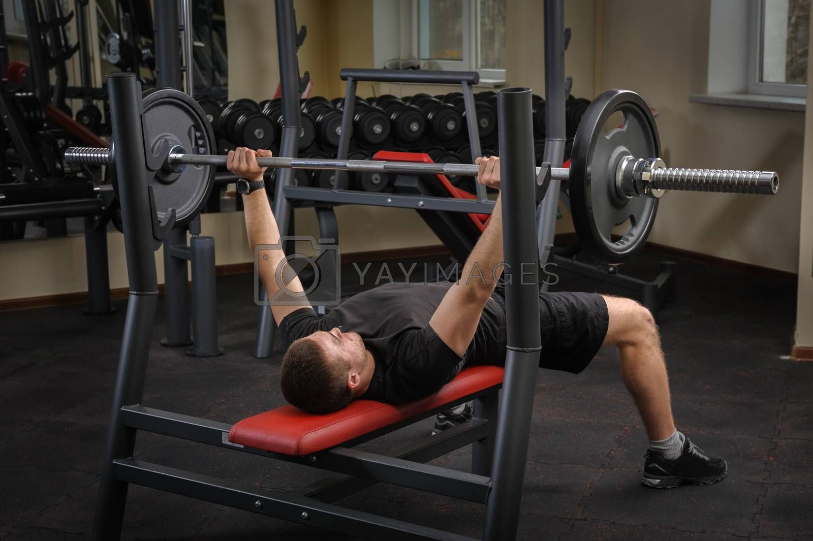 Royalty free image of young man doing bench press workout in gym by starush