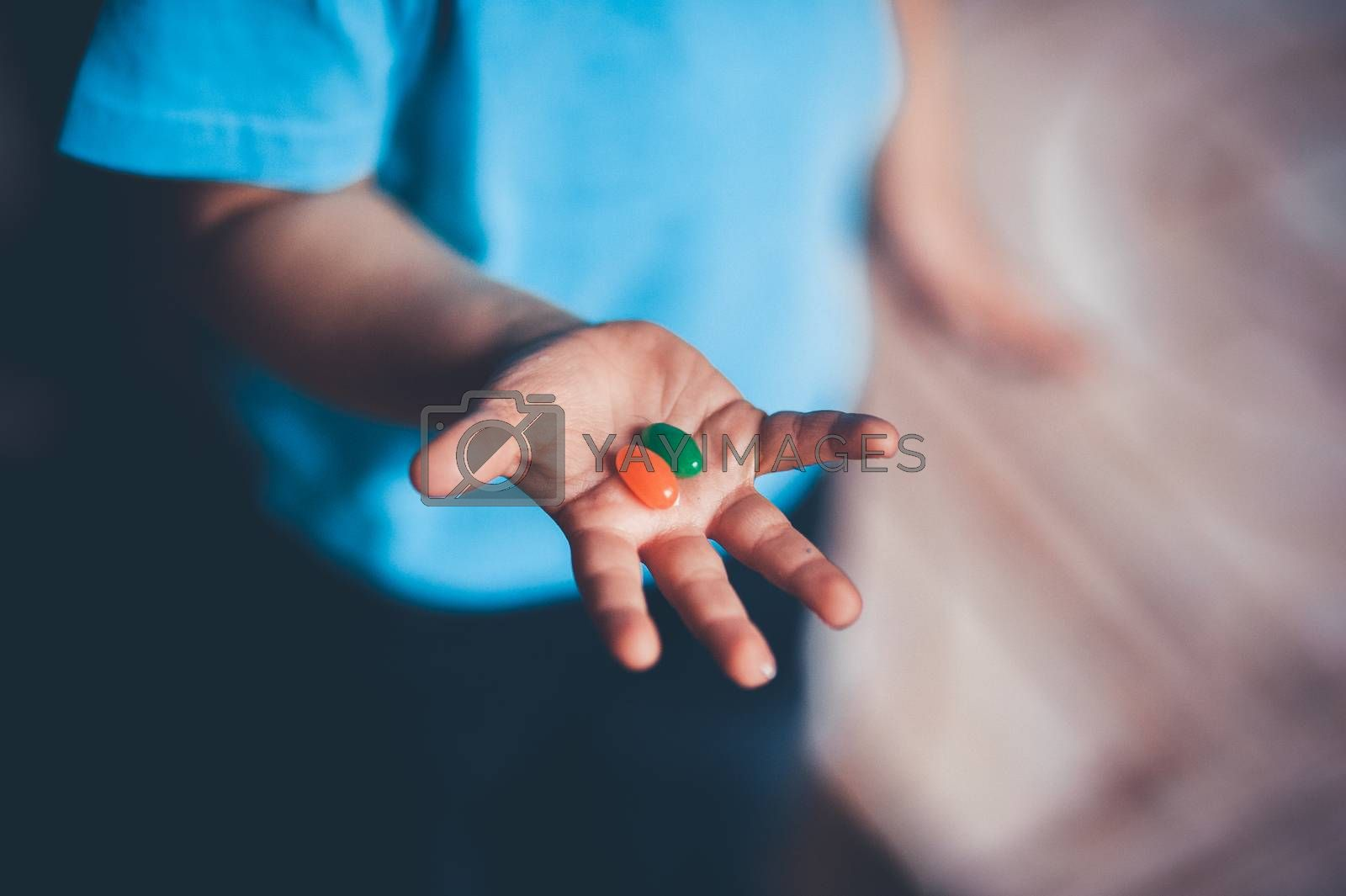 child holds candies on his open hand