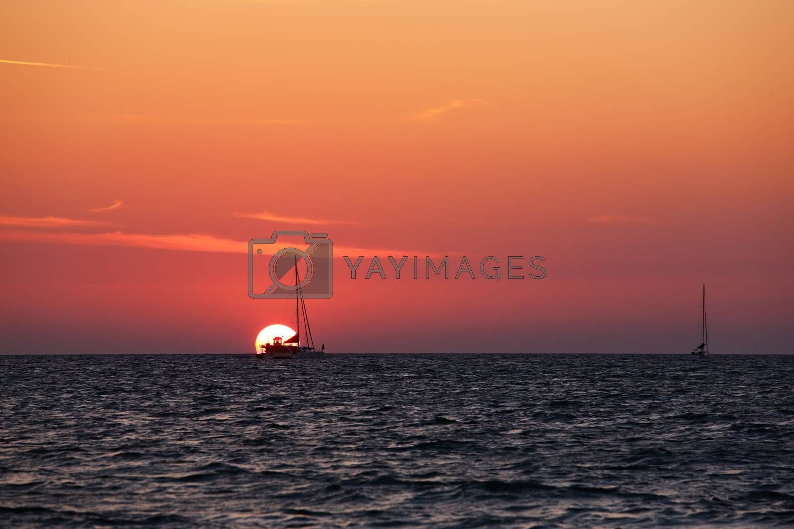 two sailboats over orange sunset at open sea. One of the boats is in the sun