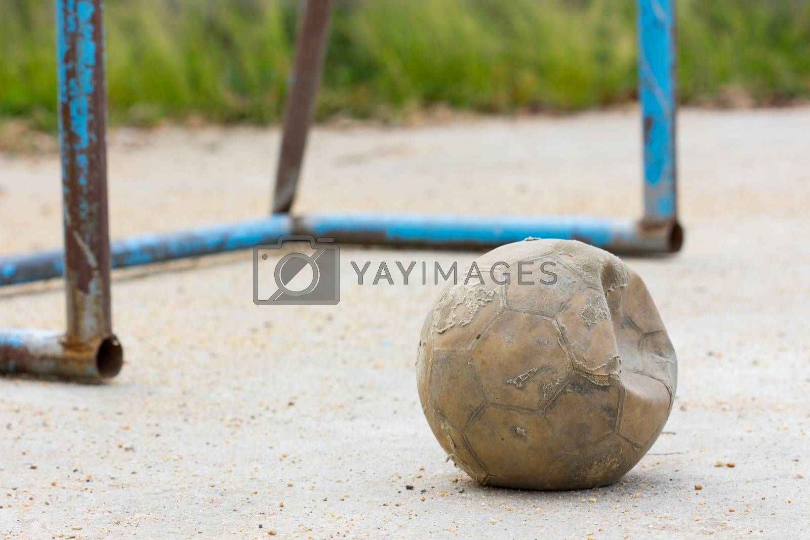 old soccer ball on concrete field with old blue goal
