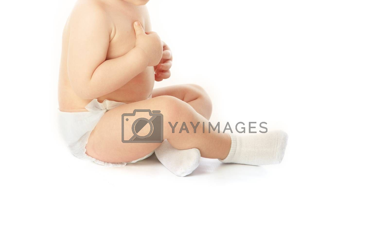 Little unrecognizable child in pampers and socks on a white background