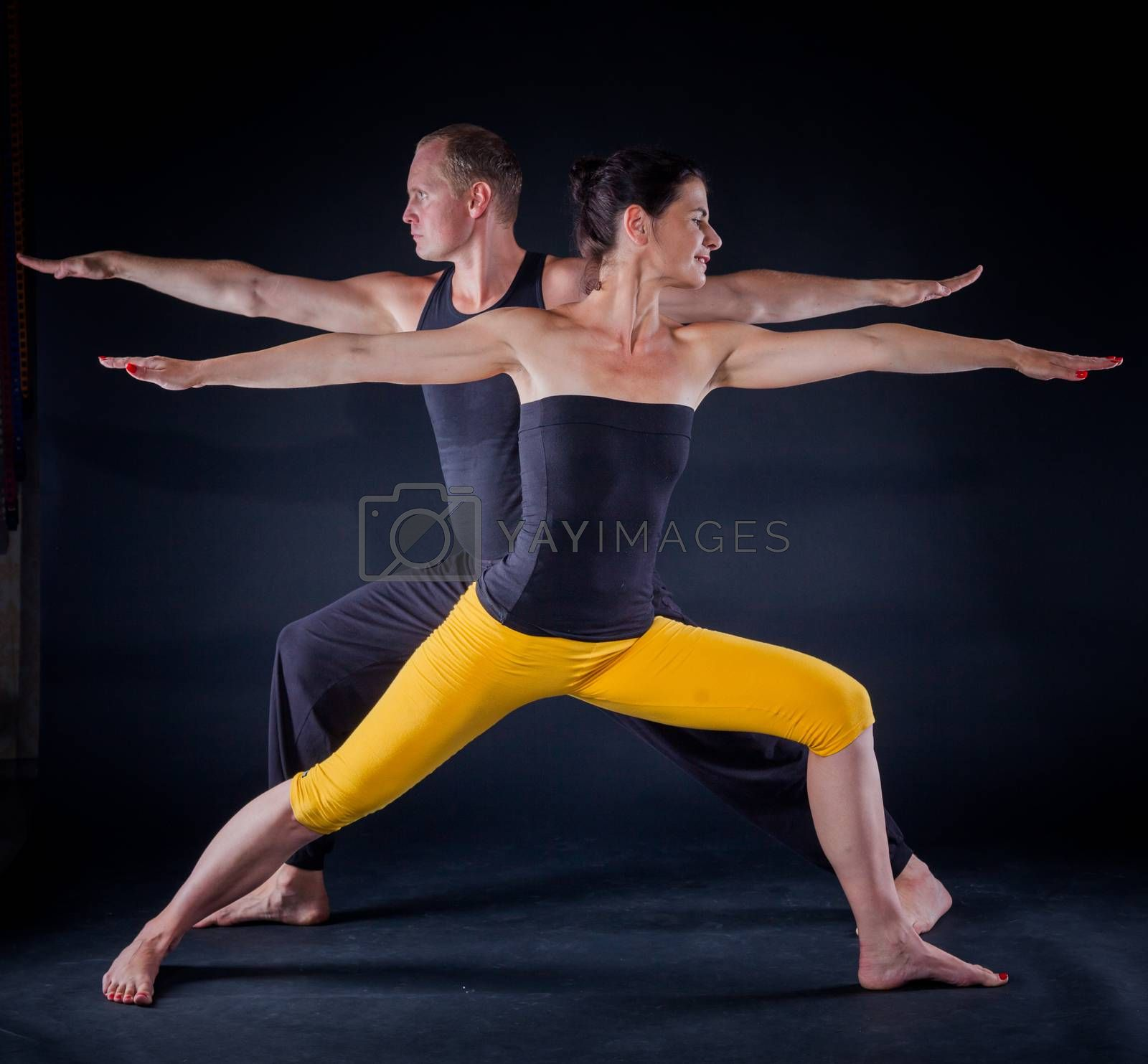 Young couple doing yoga. On the black backgraund