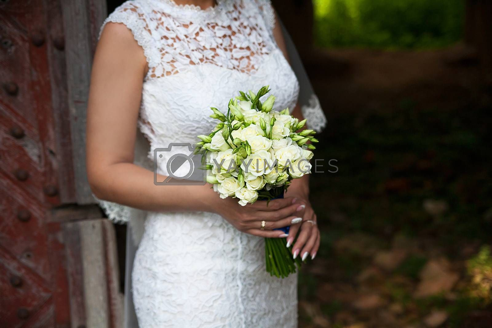 Royalty free image of Bride holding wedding flower bouquet of roses. by sfinks