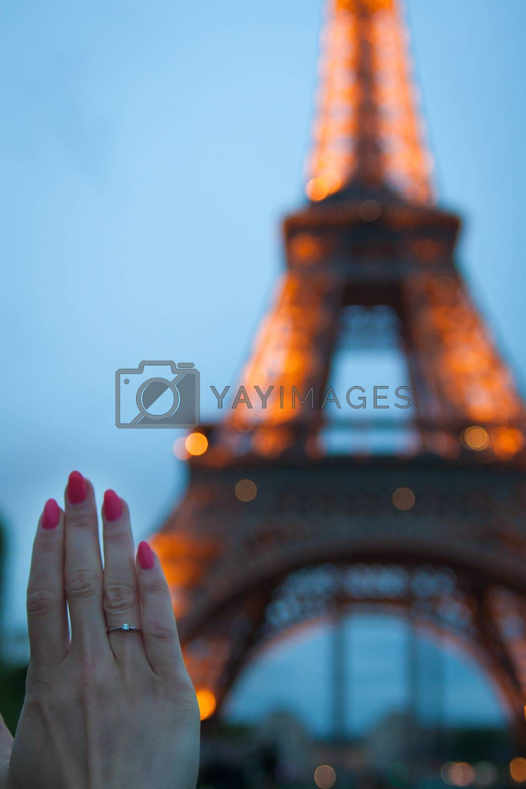 Royalty free image of Girl holds her hand with a gold ring by sfinks