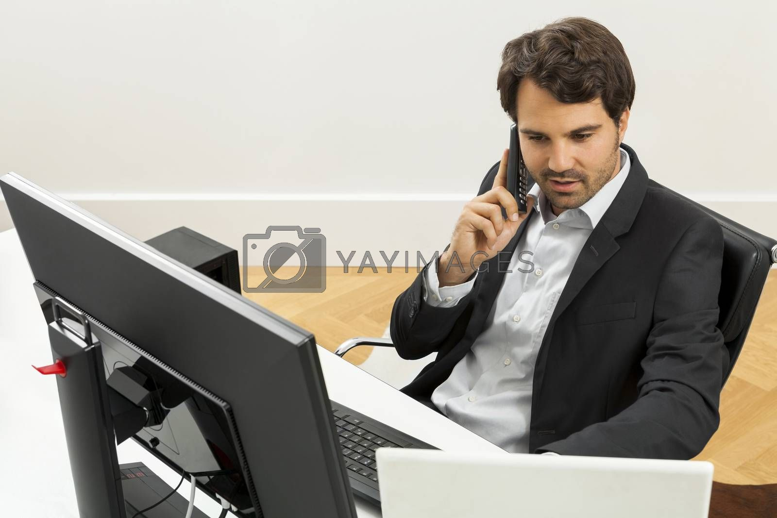 Successful businessman working in his office sitting in a chair at his desk and desktop computer listening to a call on his mobile phone, high angle side view