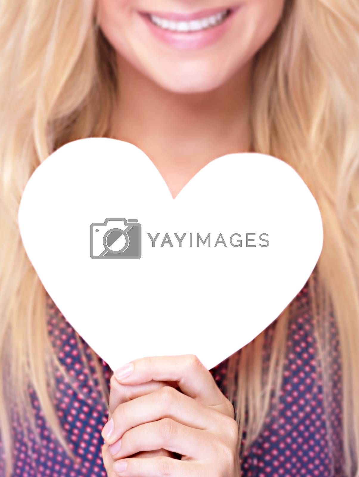 Closeup photo of happy smiling woman holding in hands white paper heart shaped greeting card, healthy lifestyle, romantic Valentine day, love or good health concept