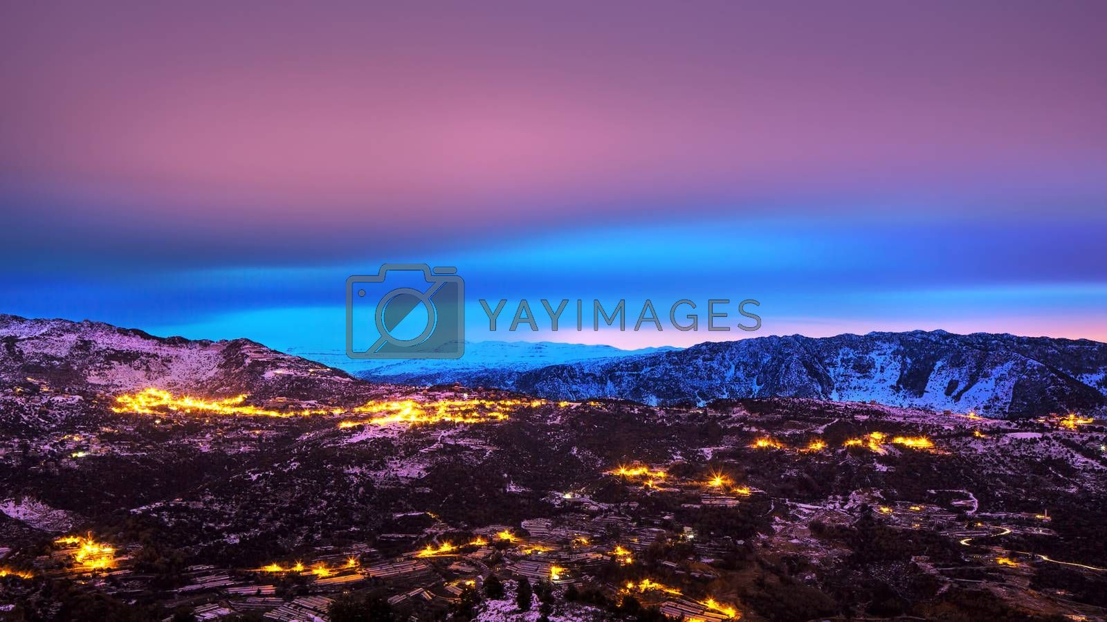 Beautiful mountains landscape, amazing pink and blue sky over mountainous glowing city, beauty of nighttime, winter holidays concept