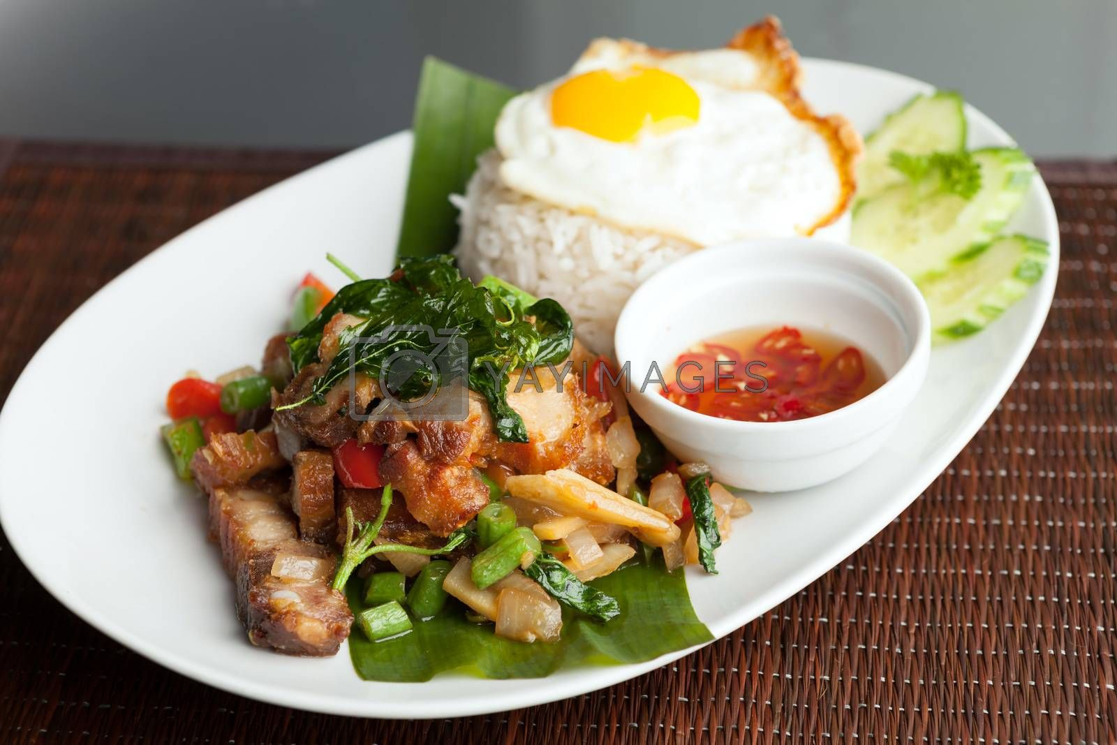 Traditional Thai dish crispy pork with a fried egg atop the jasmine rice served with chili sauce.