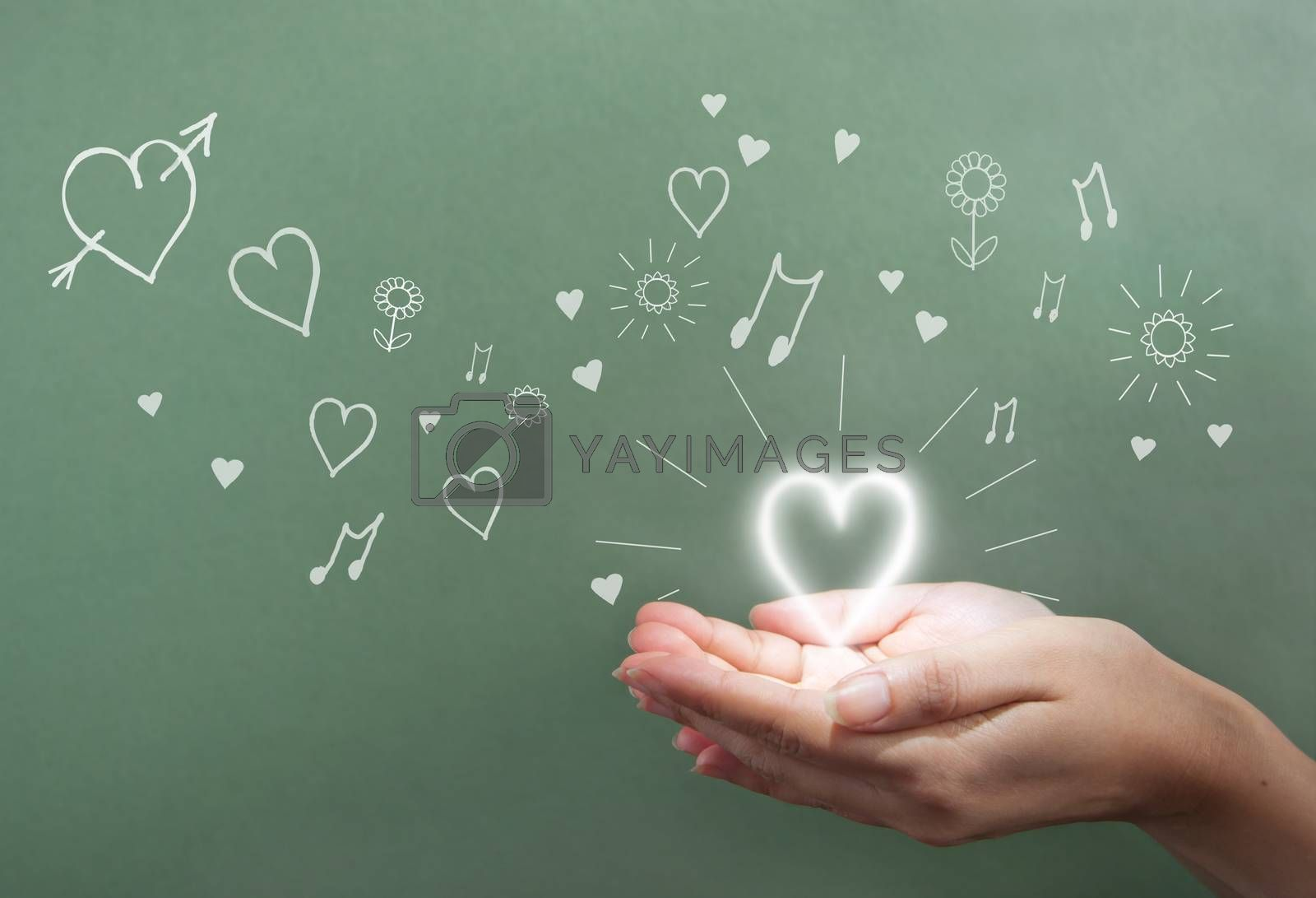Hands holding a glowing heart over a chalkboard with love symbols