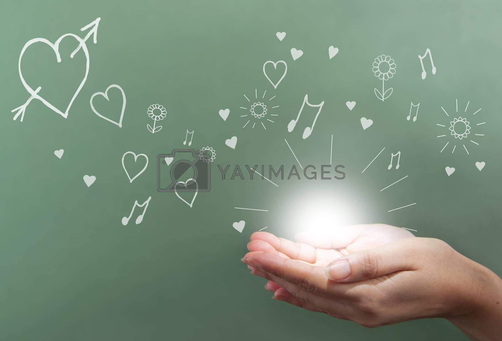 Hand holding energy ball with love symbols drawn on a chalkboard in the background