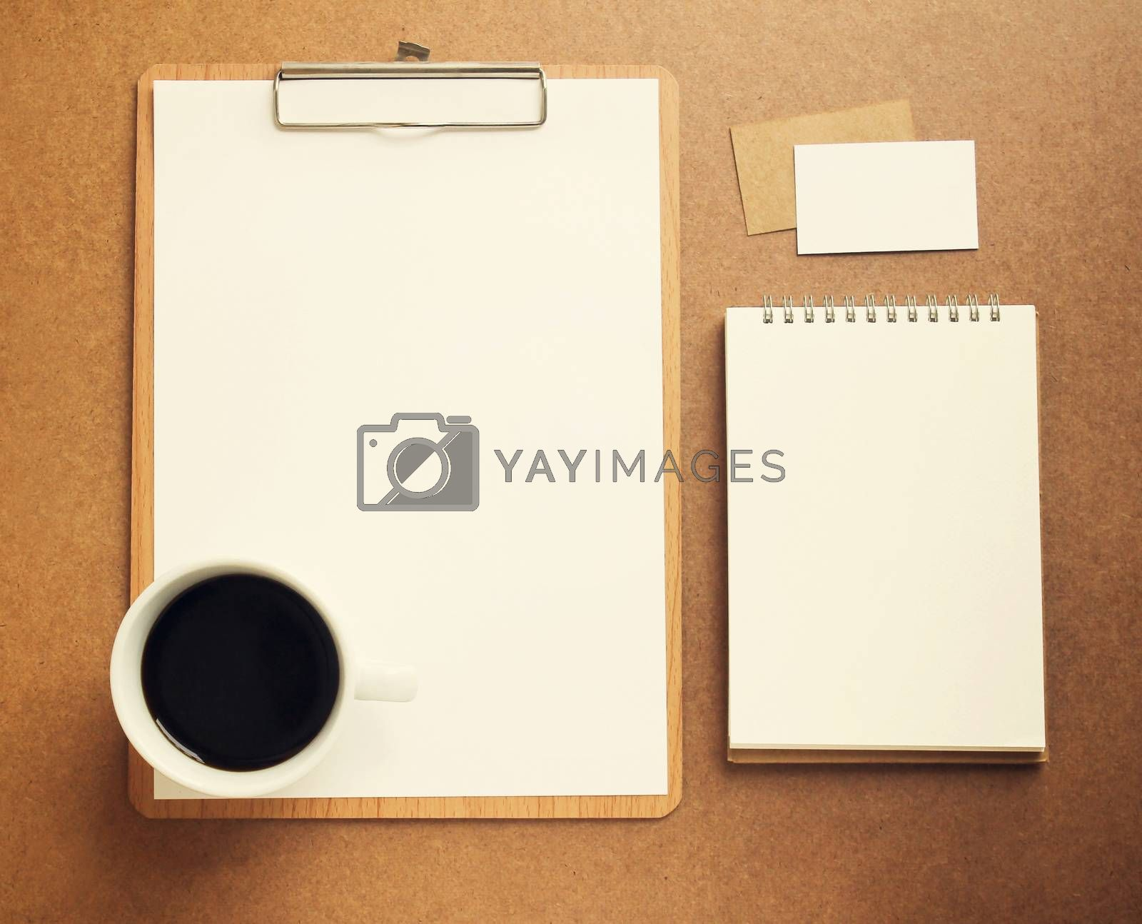 Blank white paper on clipboard and notebook with cup of coffee, retro filter effect