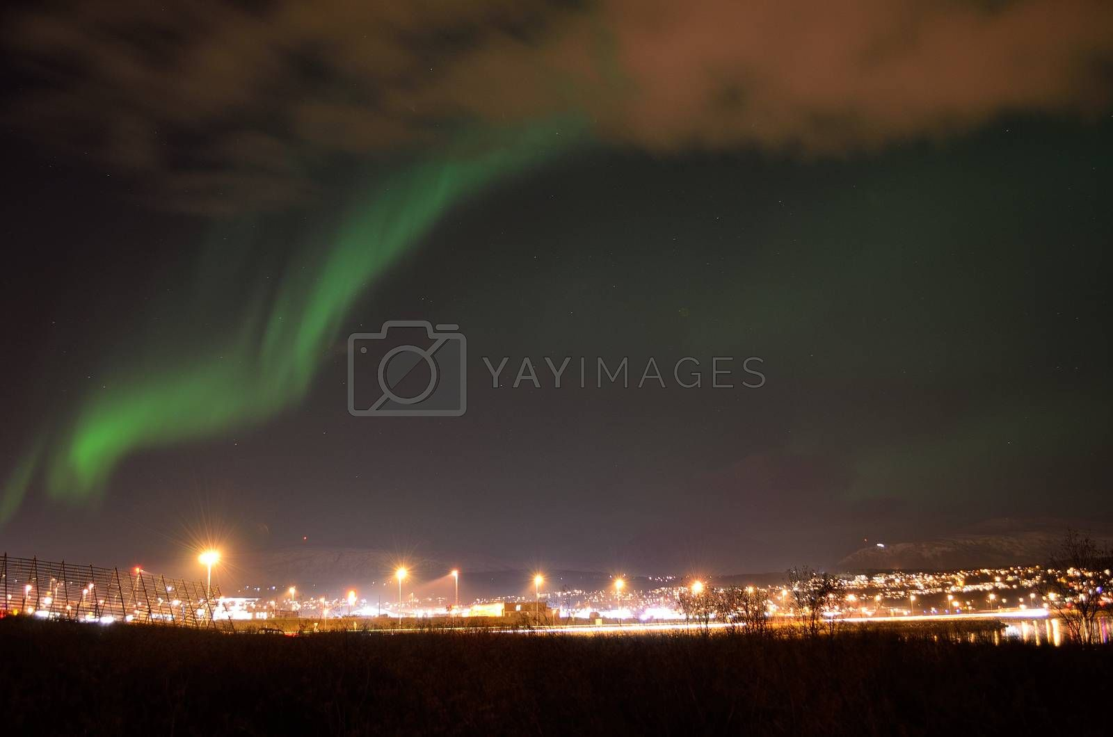 aurora borealis over city island of tromsoe in late autumn night