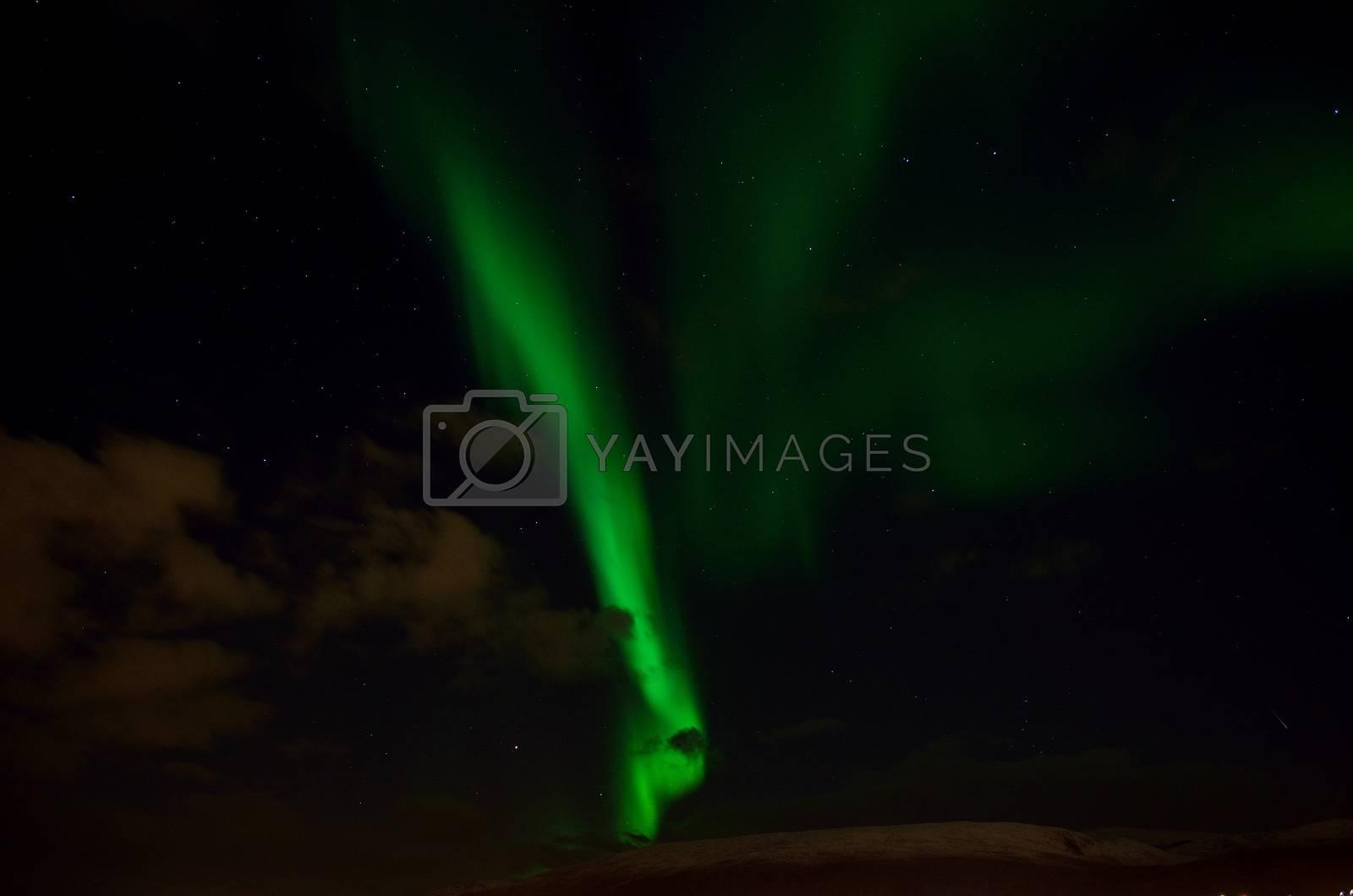 strong aurora borealis over snowy mountain in autumn