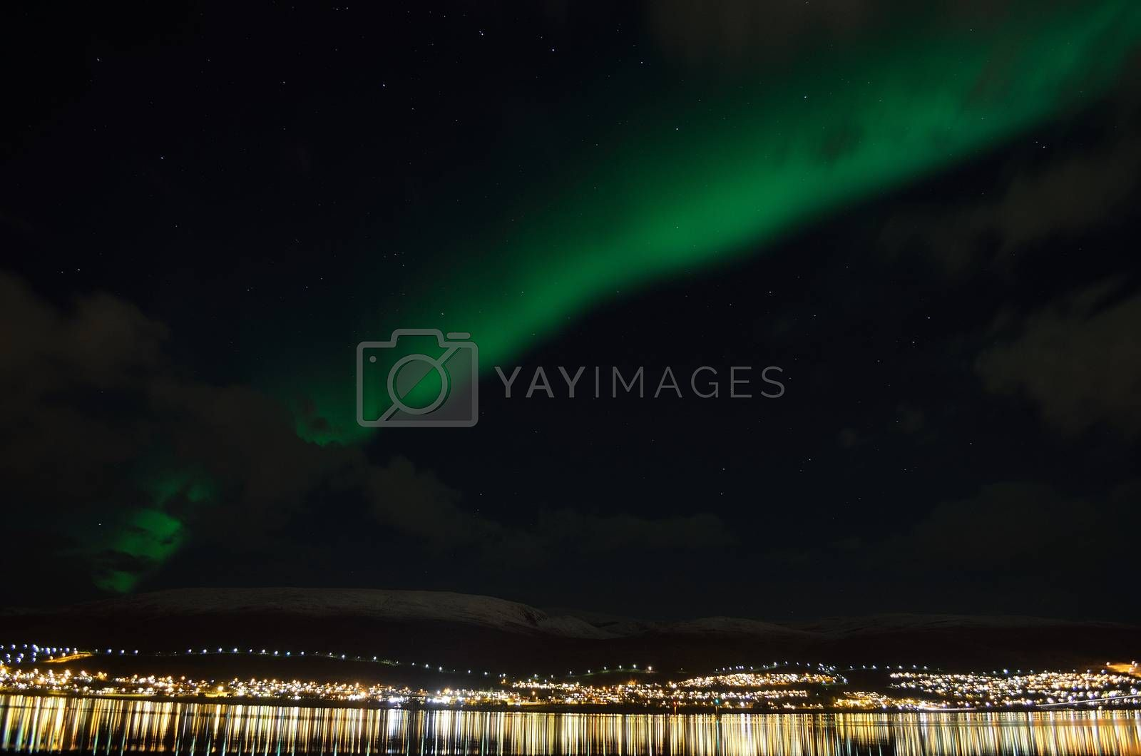 aurora borealis over arctic circle settlement reflecting in fjord water over snowy mountain