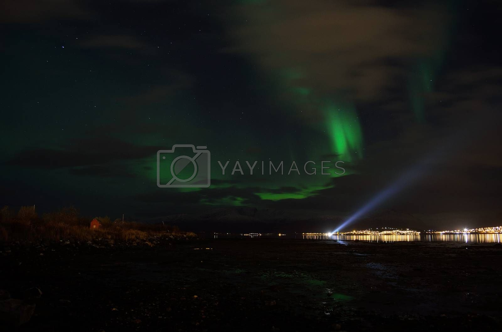 aurora borealis over a boat searchlight on the fjord reflecting of the surface with illuminated settlement in the background