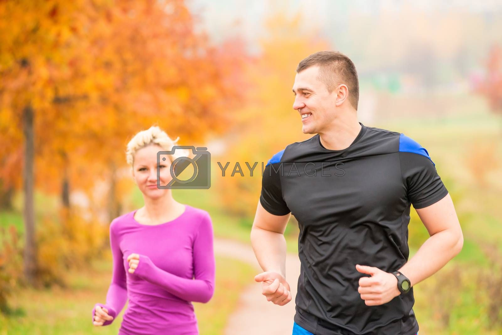 healthy lifestyle - jogging. a man and a woman running in the mo by Labunskiy K.