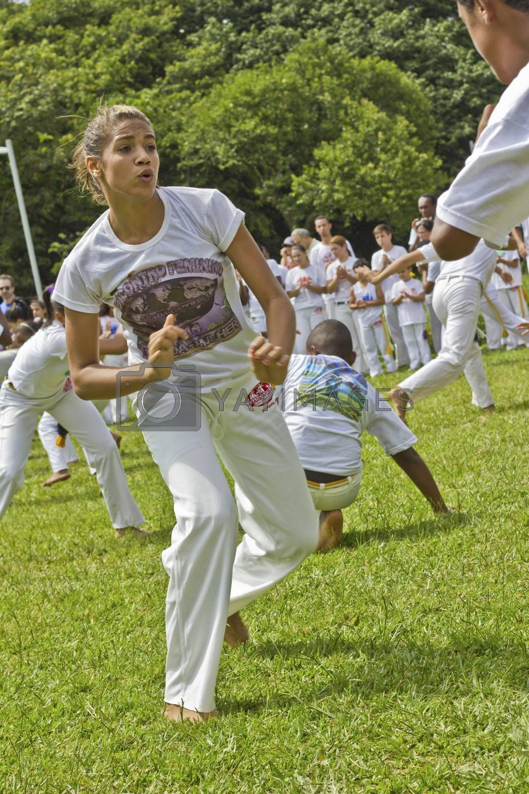 SAO PAULO, BRAZIL - FEBRUARY 01, 2015: An unidentified girl fights capoeira in a circle of people with traditional samba music on the grass of Ibirapuera Park at Sao Paulo Brazil.
