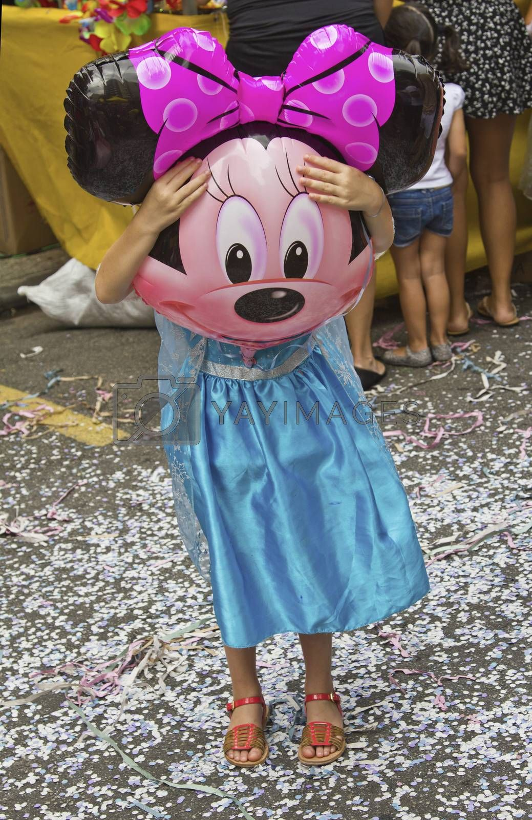 SAO PAULO, BRAZIL - JANUARY 31, 2015: An unidentified girl dressed like a princess with a Minie ballon in front her face participate in the annual Brazilian street carnival dancing and singing samba.