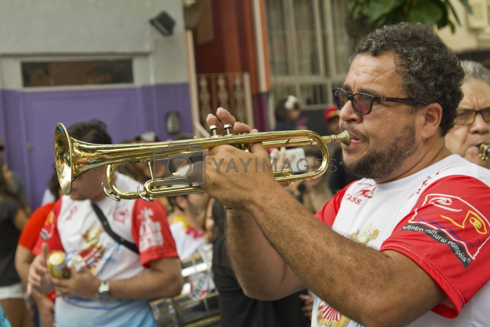 SAO PAULO, BRAZIL - JANUARY 31, 2015: An unidentified man playing trumpet in a traditional samba band participate in the annual Brazilian street carnival.