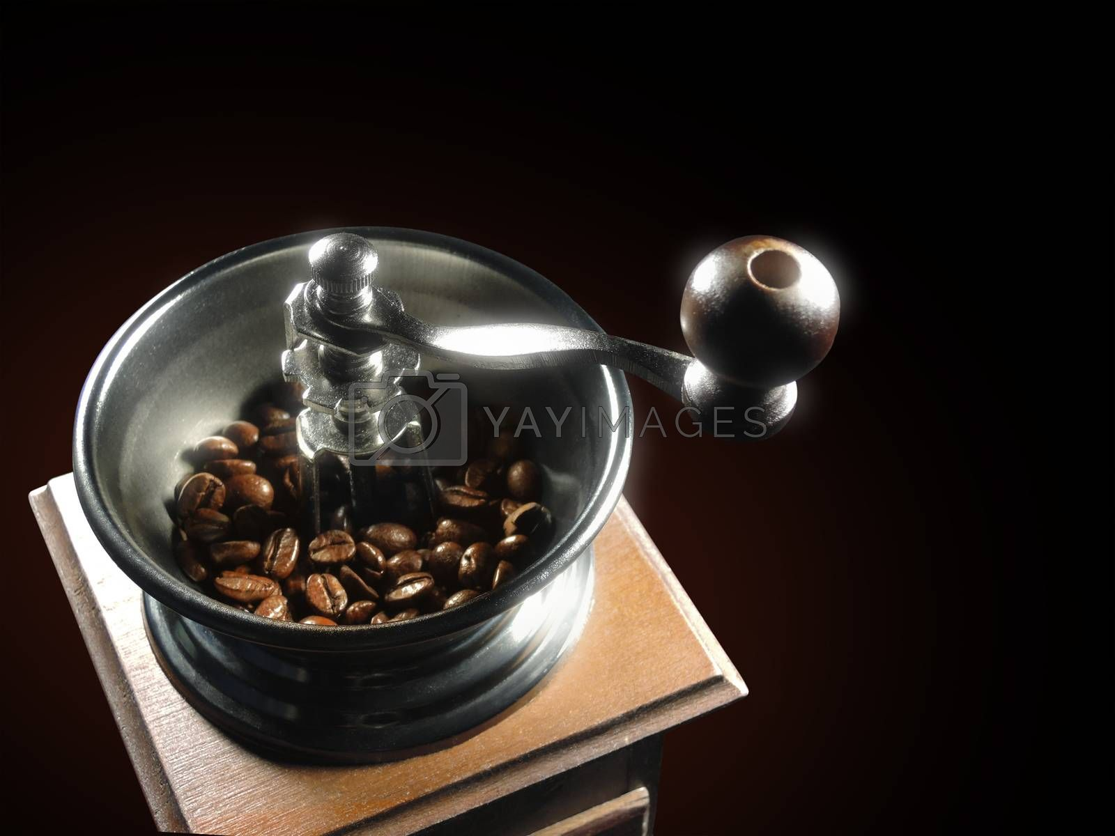 coffee grinder with grains on a black background