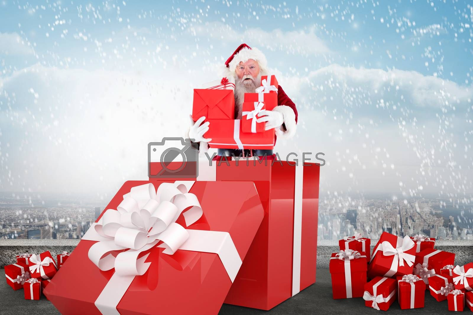 Santa standing in large gift against balcony overlooking city
