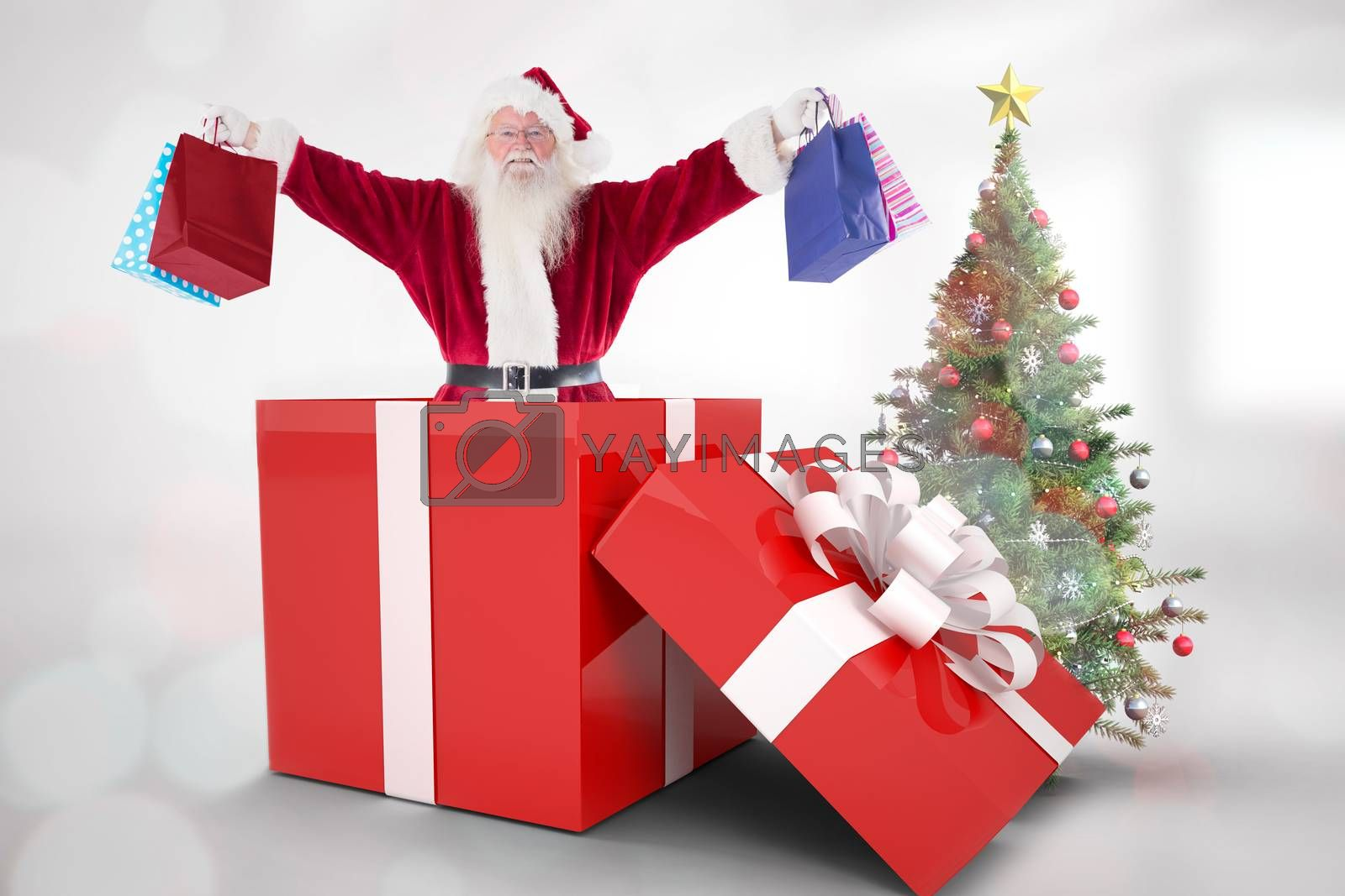 Santa standing in large gift against christmas tree in bright room
