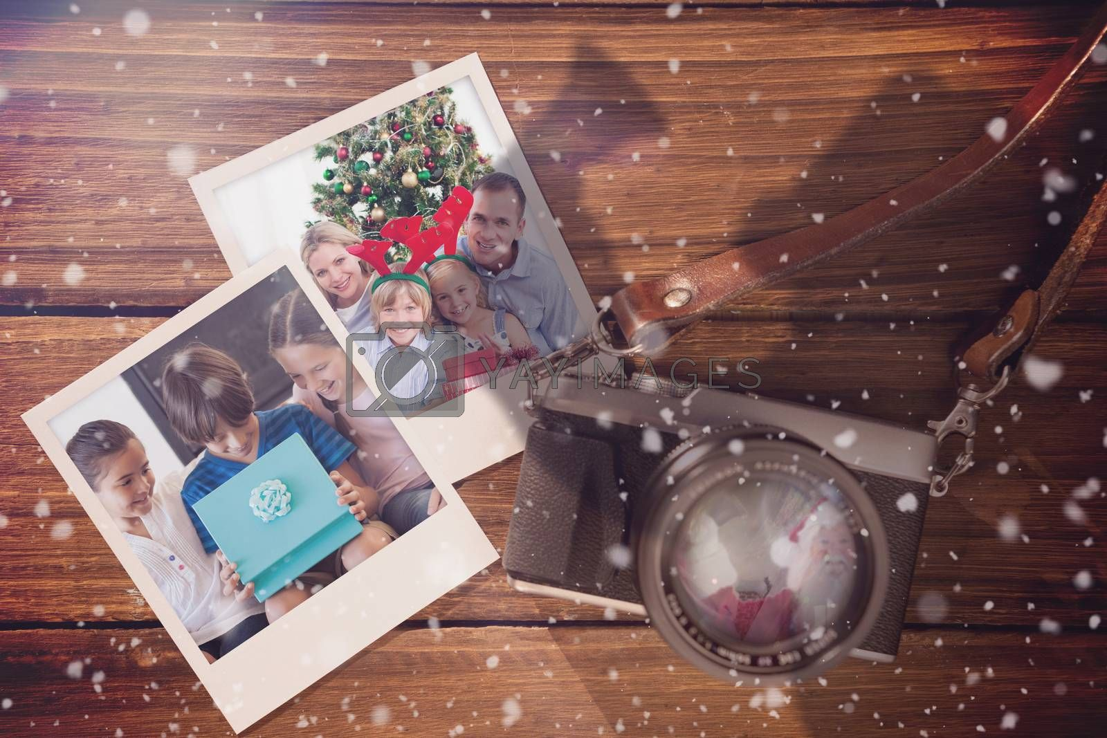 Composite image of christmas memories  against instant photos on wooden floor