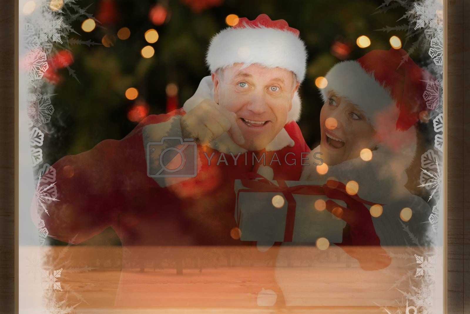 Festive mature couple holding gift against desk with christmas tree in background