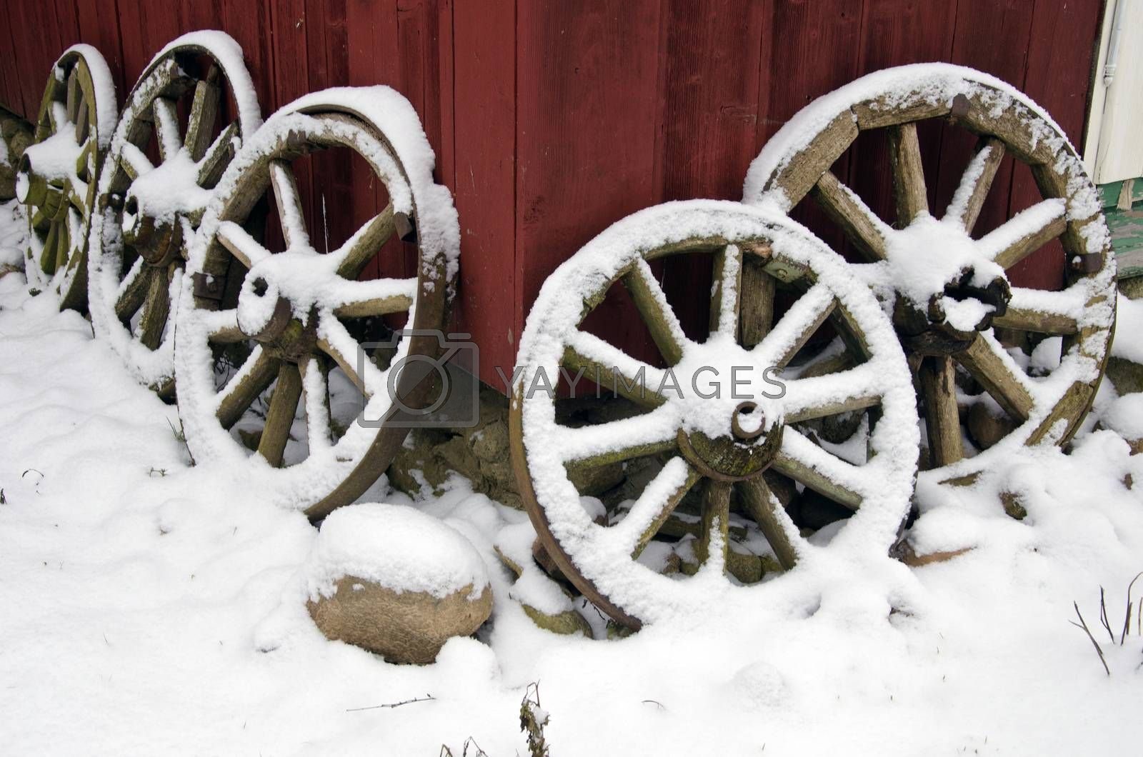 antique horse carriage wheels collection near farm house and winter snow