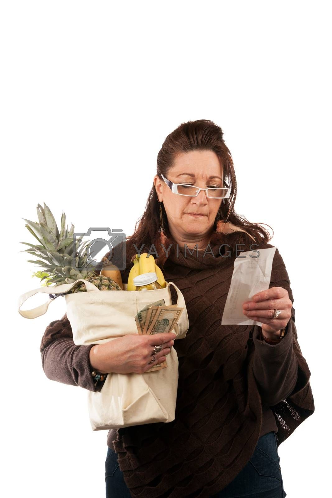 Middle aged woman carefully examining her register receipt reviewing her grocery shopping bill.