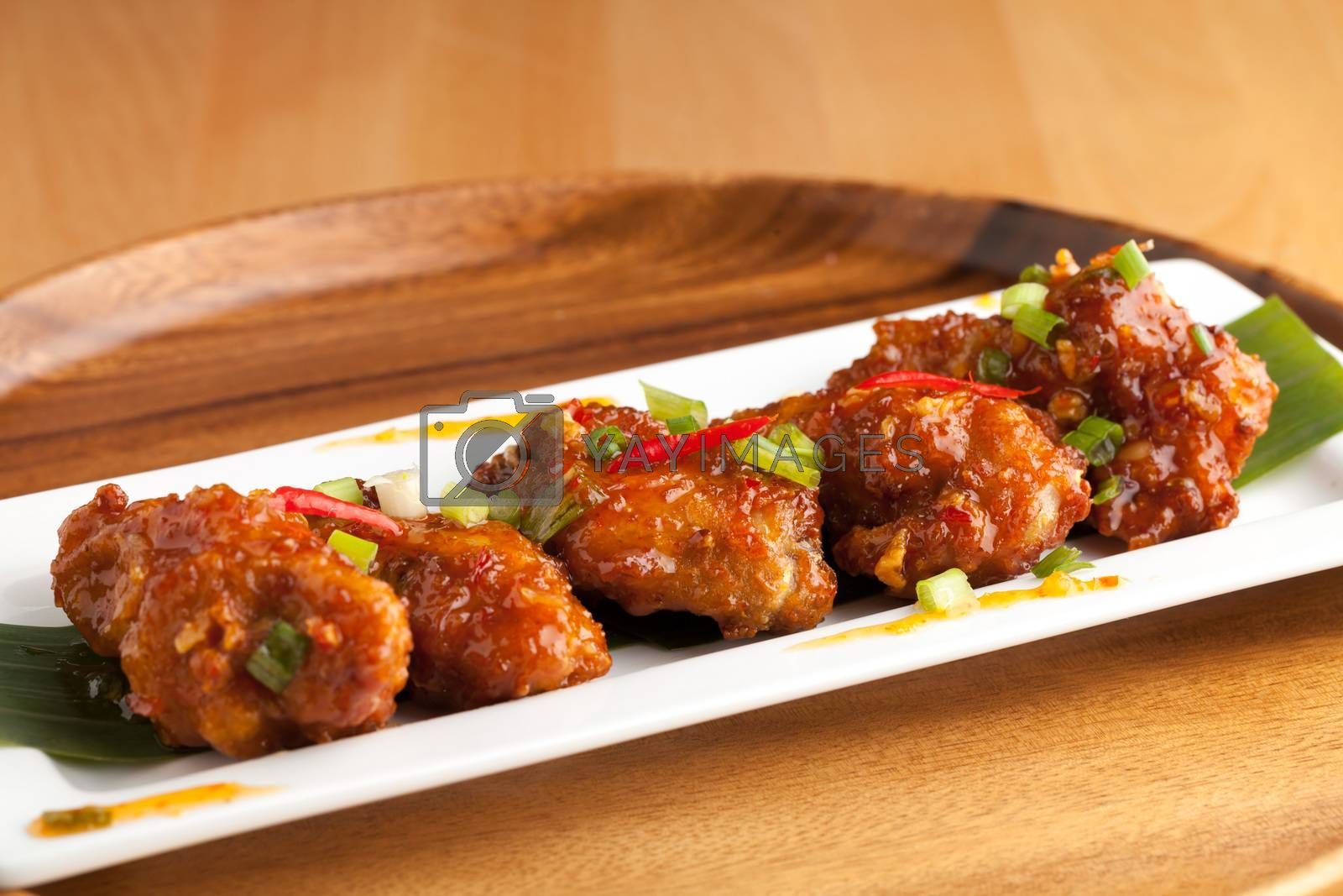 Thai style hot and spicy chicken wings appetizer on a contemporary white plate.