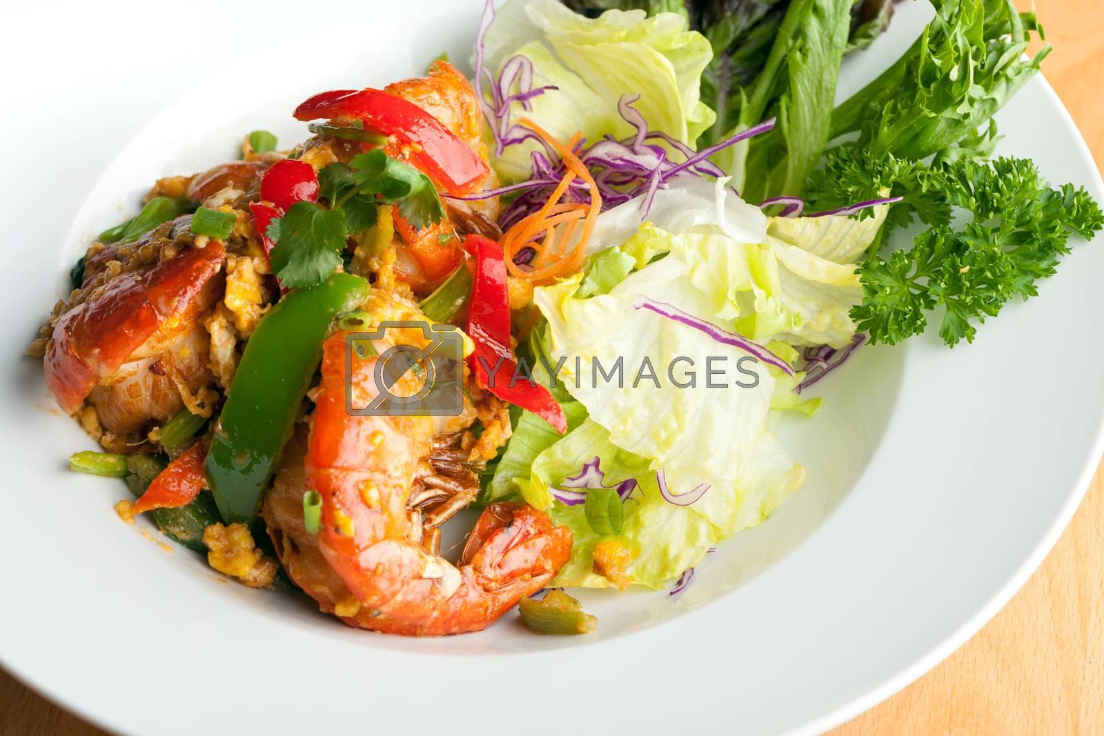 Thai jumbo shrimp salad on a round white plate. Shallow depth of field.