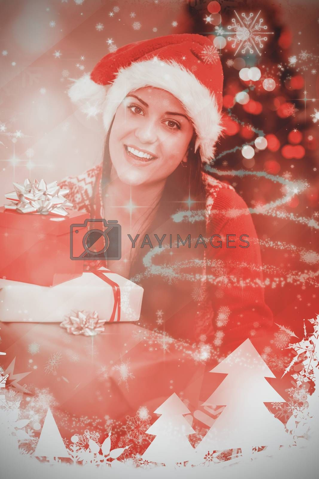 Festive brunette smiling at camera against glittering christmas tree design
