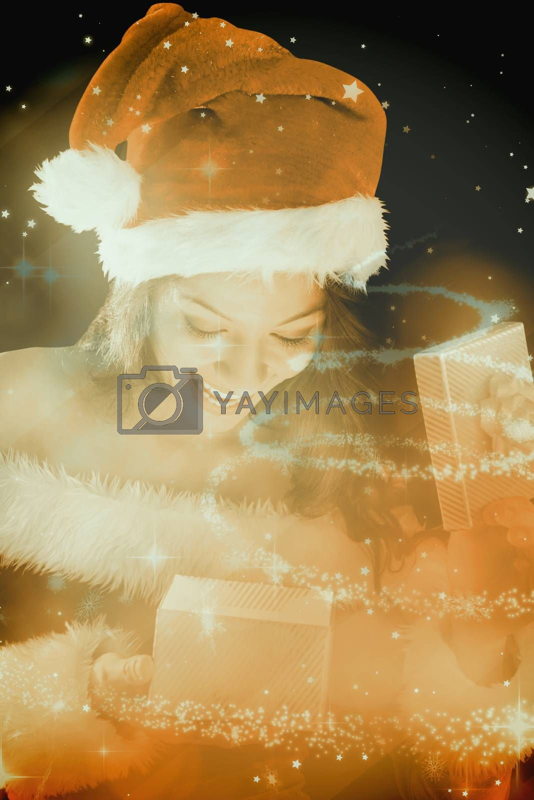 Pretty brunette in santa outfit opening gift against glittering christmas tree design