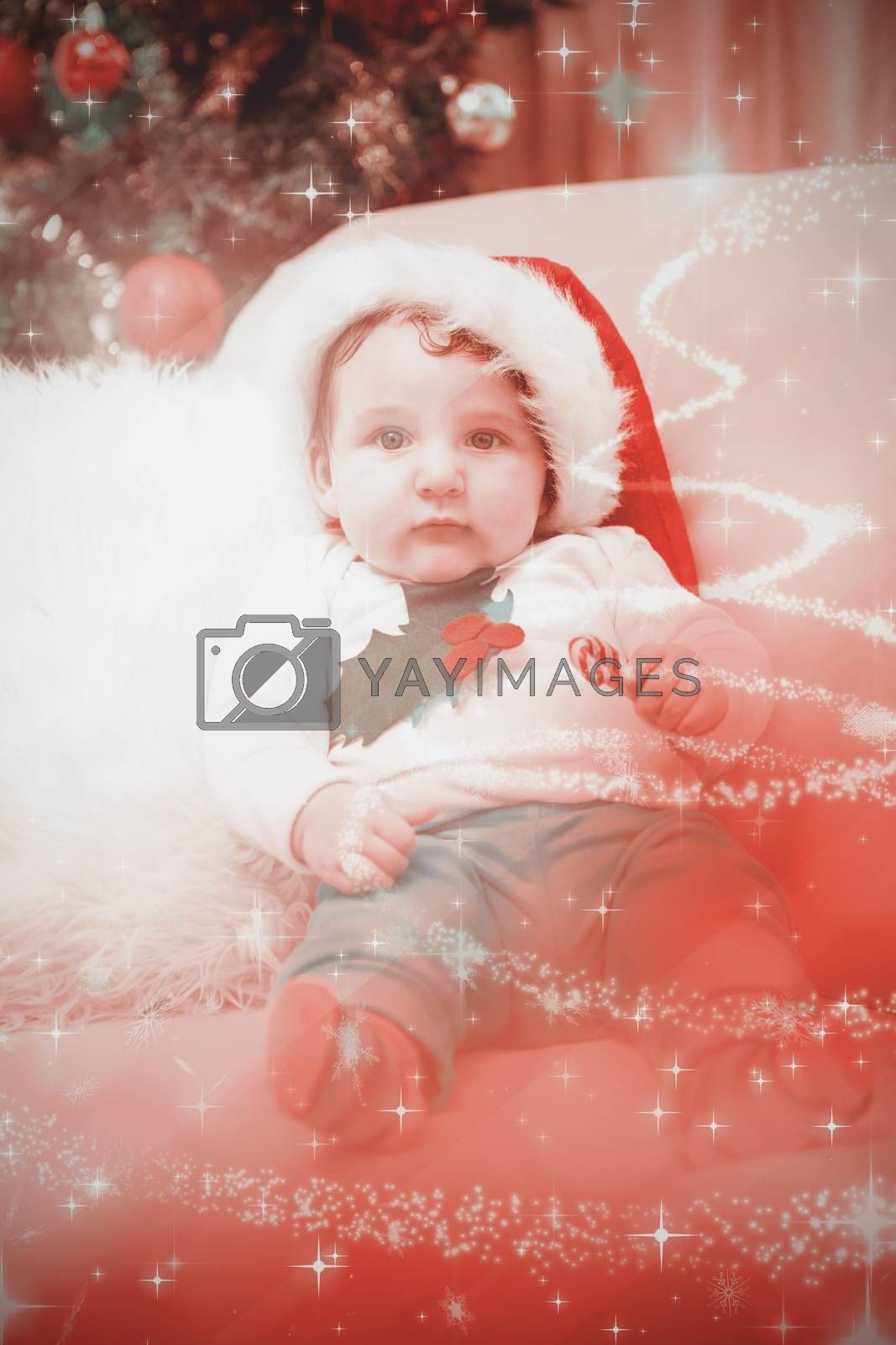 Cute baby boy on couch at christmas against glittering christmas tree design