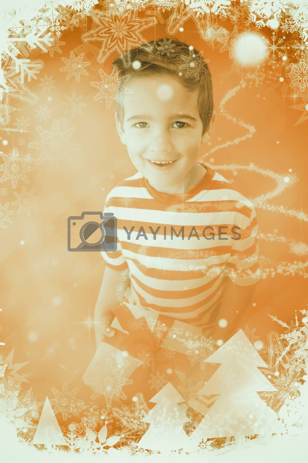 Festive little boy holding a gift against glittering christmas tree design